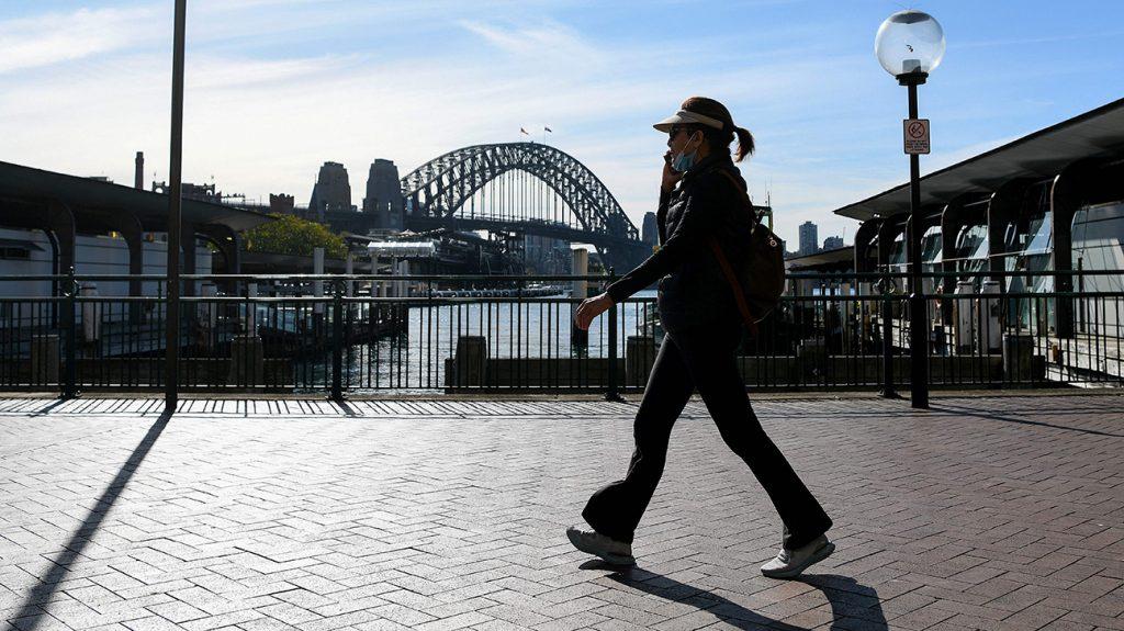 Moteris, užsidėjusi veido kaukę, eina pro tiltą.