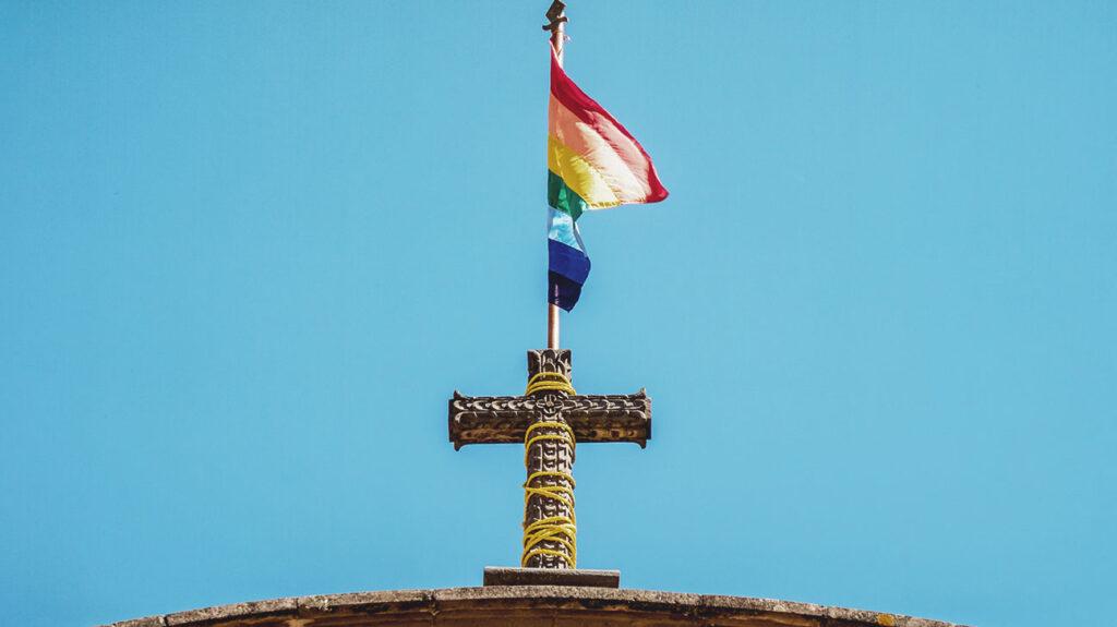 Bandeira de arco-íris no topo de uma igreja