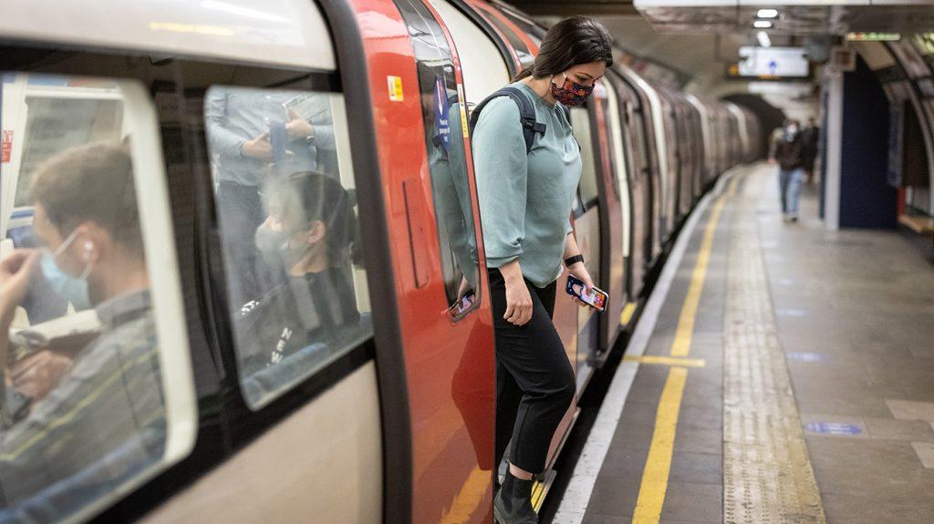 Kobieta z telefonem komórkowym w ręku schodzi z podziemi na peron