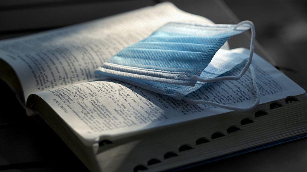 μάσκα τοποθετημένη σε ανοιχτό βιβλίο