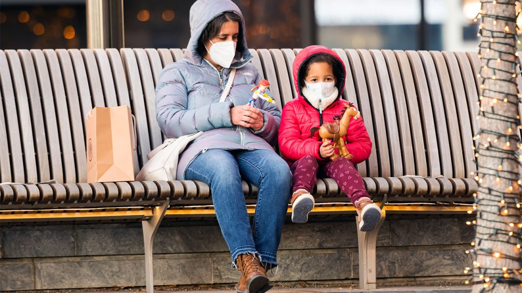 nënë dhe fëmijë me maska në stacionin e autobusit