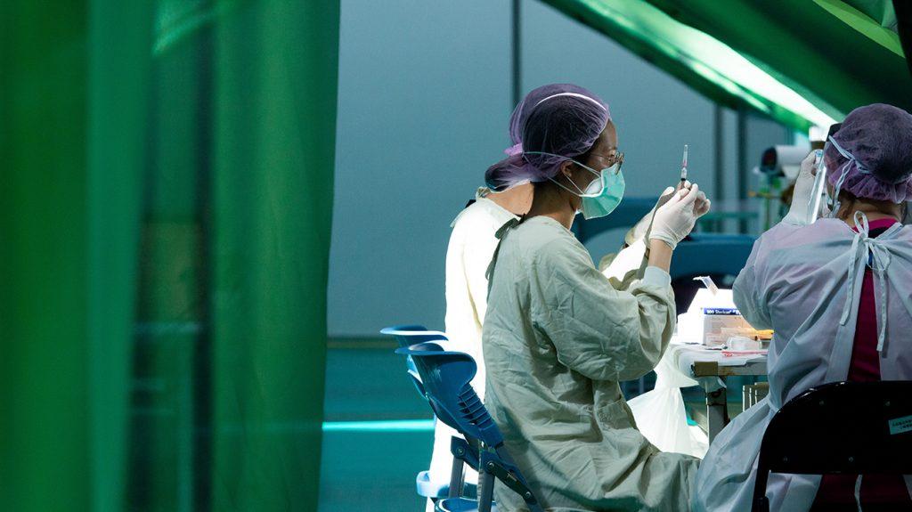 επαγγελματίες υγείας που φορούν μάσκες, προετοιμάζουν εμβόλια