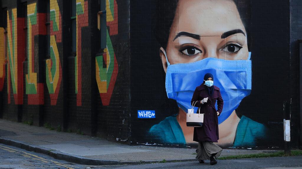 LONDRA, ANGLIA - 21 APRILIE: O femeie îmbrăcată cu o mască de față trece pe lângă o piesă de artă stradală care înfățișează un lucrător al NHS pe 21 aprilie 2020 în zona Shoreditch din Londra, Anglia. Guvernul britanic a extins restricțiile de blocare introduse pentru prima dată pe 23 martie, menite să încetinească răspândirea COVID-19. (Fotografie de Andrew Redington / Getty Images)