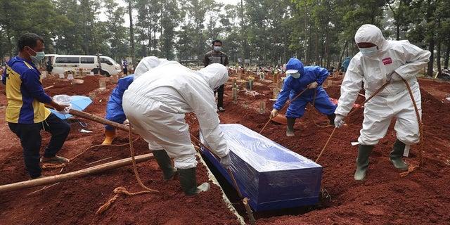 14 de julho de 2021: Trabalhadores com equipamentos de proteção abaixam o caixão de uma vítima COVID-19 em uma sepultura para sepultamento no Cemitério Cipenjo em Bogor, Java Ocidental, Indonésia. O quarto país mais populoso do mundo foi duramente atingido por uma explosão de casos COVID-19 que sobrecarregaram hospitais na ilha principal de Java.