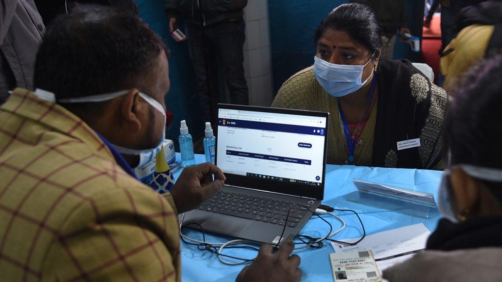 άτομα στην Ινδία που προσπαθούν να κλείσουν ένα εμβόλιο στο φορητό τους υπολογιστή