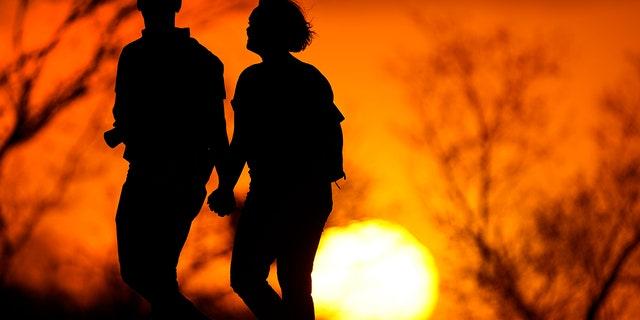 Pár sa prechádza parkom pri západe slnka v Kansas City, Mo 10. marca 2021. (AP Photo / Charlie Riedel, spis)