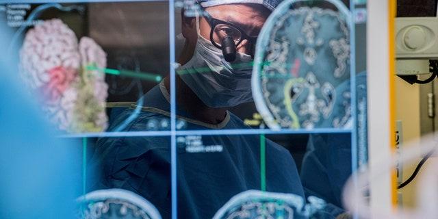 Σε αυτήν τη φωτογραφία του 2017 που παρείχε το Πανεπιστήμιο της Καλιφόρνια στο Σαν Φρανσίσκο, ο νευροχειρουργός Δρ Edward Chang αντικατοπτρίζεται σε μια οθόνη υπολογιστή που εμφανίζει εγκεφαλικές σαρώσεις καθώς εκτελεί χειρουργική επέμβαση στο UCSF.