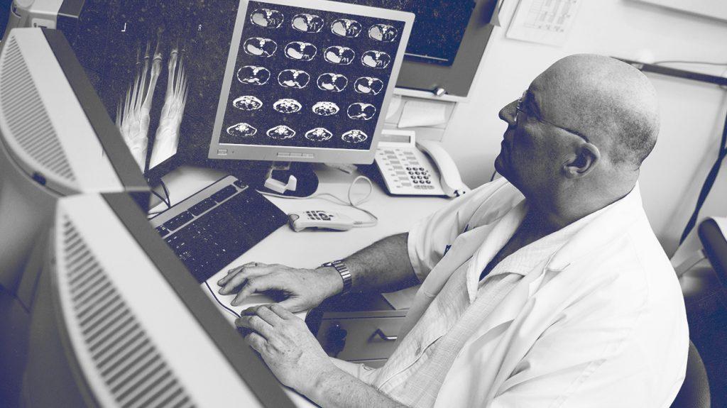 lekár vyšetrujúci skeny na počítači