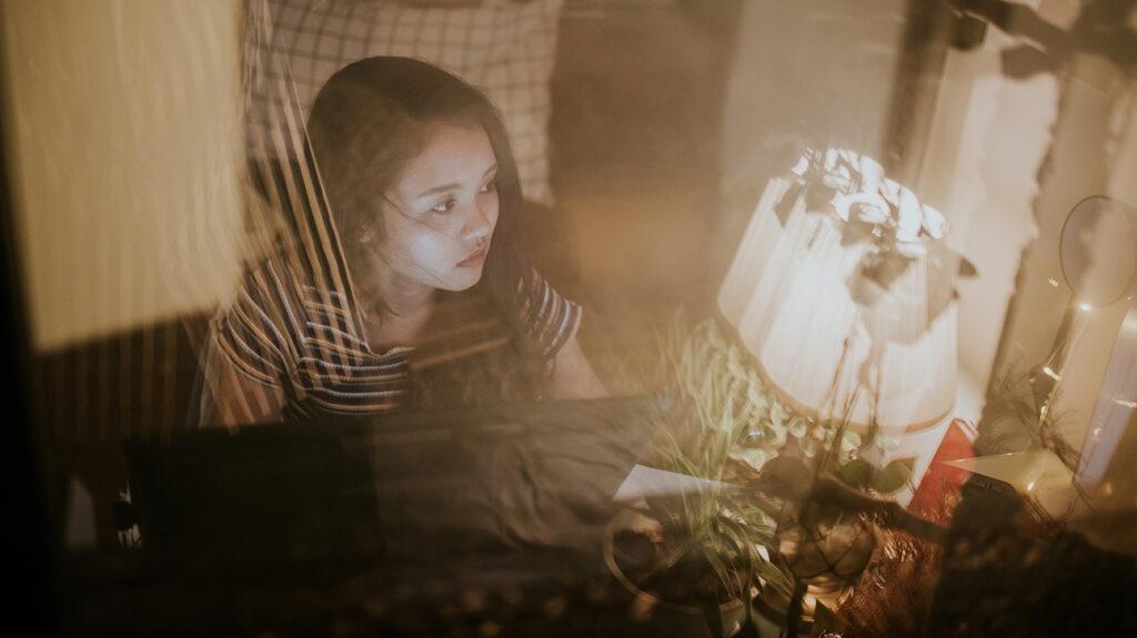 Zahmlený obraz unavenej ženy pozerajúcej sa na svoju pracovnú lampu