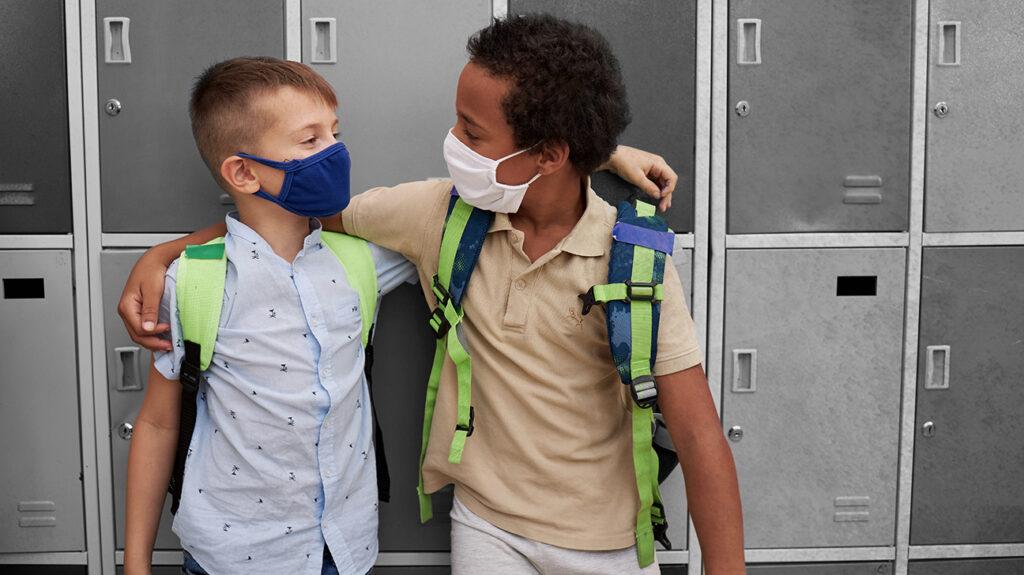 μικρά παιδιά που φορούν μάσκες αγκαλιά