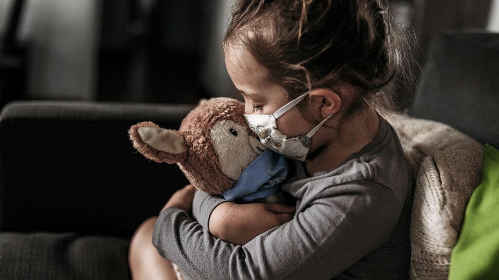 dítě v masce líbající svého plyšového medvěda