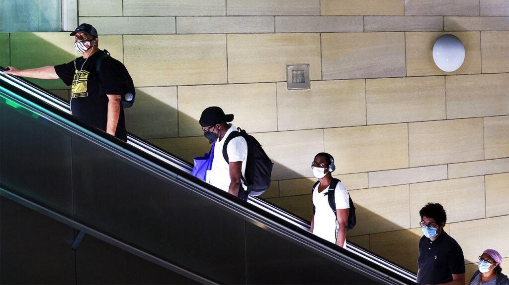 njerëzit që mbajnë maska duke qëndruar të distancuar shoqërisht në një shkallë lëvizëse