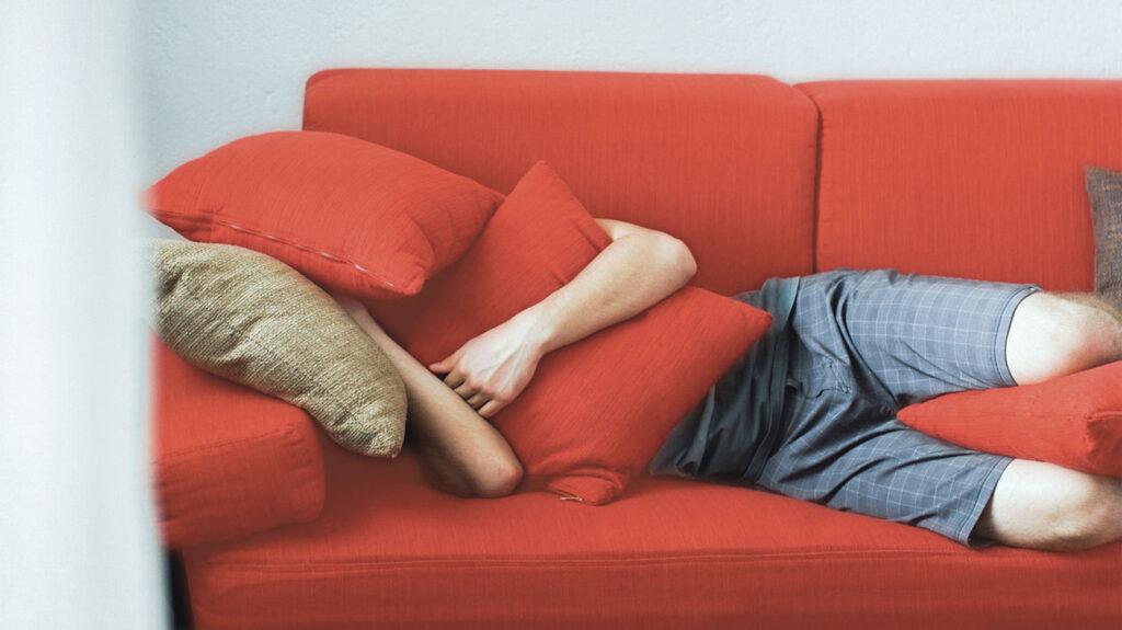Κάποιος κοιμάται σε έναν καναπέ κάτω από κόκκινα μαξιλάρια