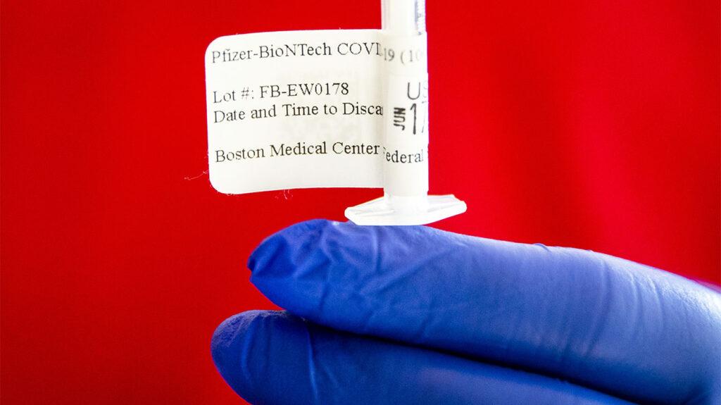zblízka rukavic držící vakcínu s připojeným štítkem