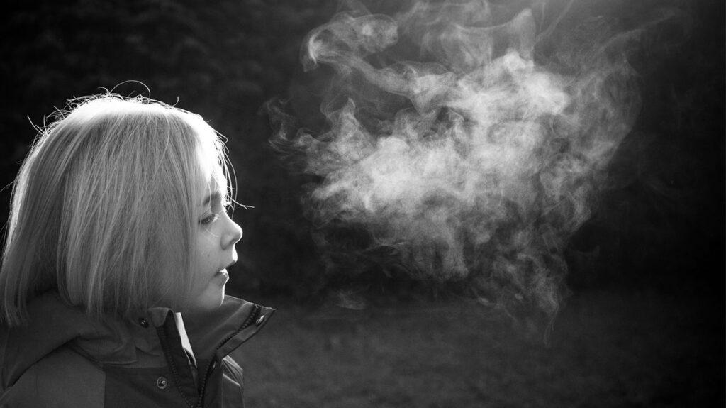 Kind ademen op een koude dag in zwart-wit