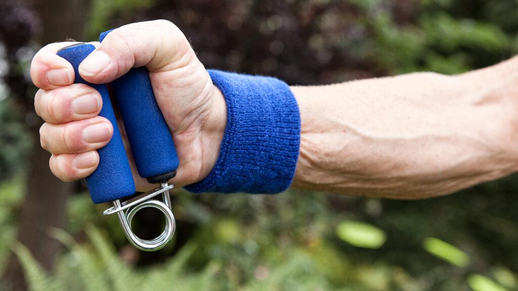 Zblízka ruky uchopení posilovacího cvičebního zařízení