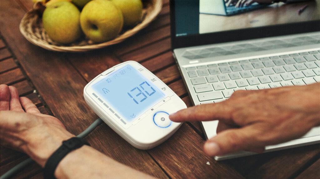 Κάποιος ελέγχει την αρτηριακή του πίεση χρησιμοποιώντας μια ψηφιακή συσκευή στο σπίτι