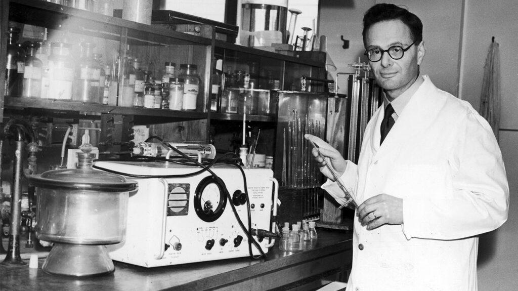 Een wetenschapper poseert met laboratoriumapparatuur.