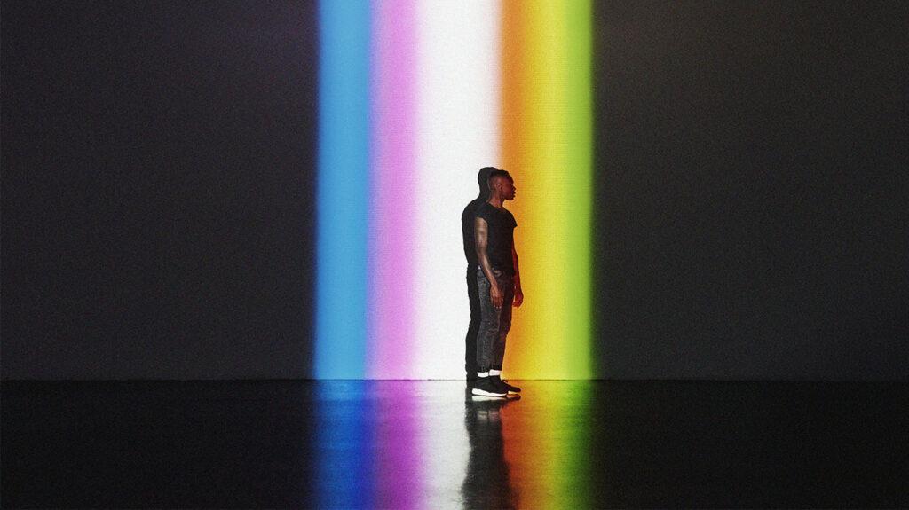 Noen som står på scenen med regnbue belysning i bakgrunnen